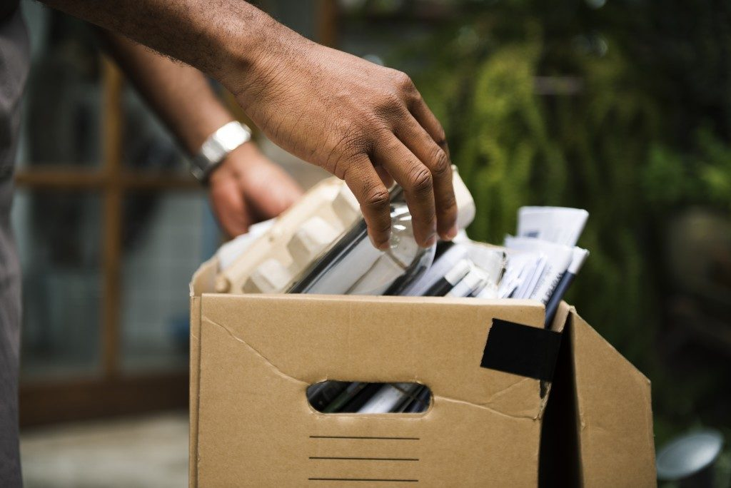 person piling up things to recycle in a box