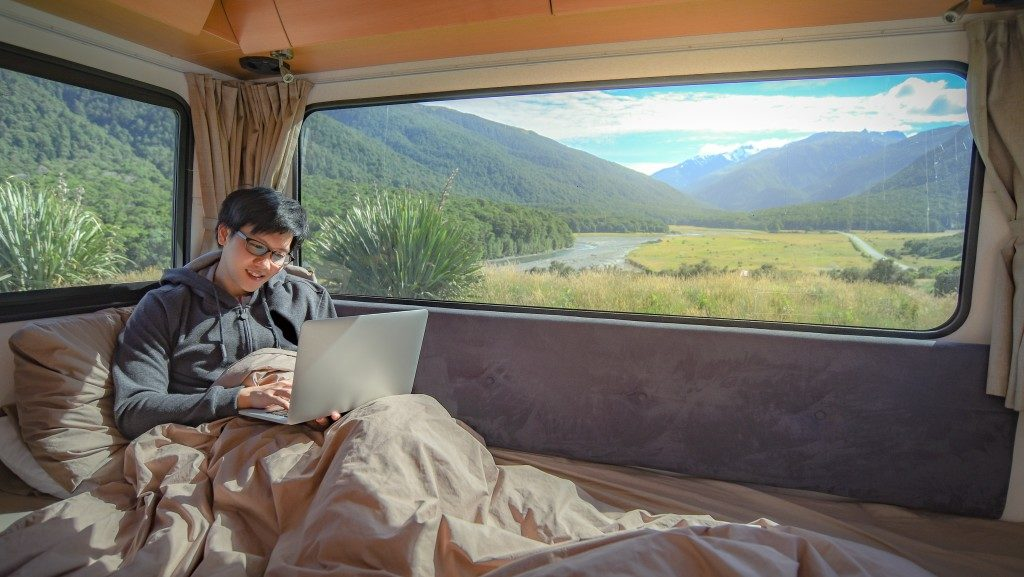 Man using laptop in camper van