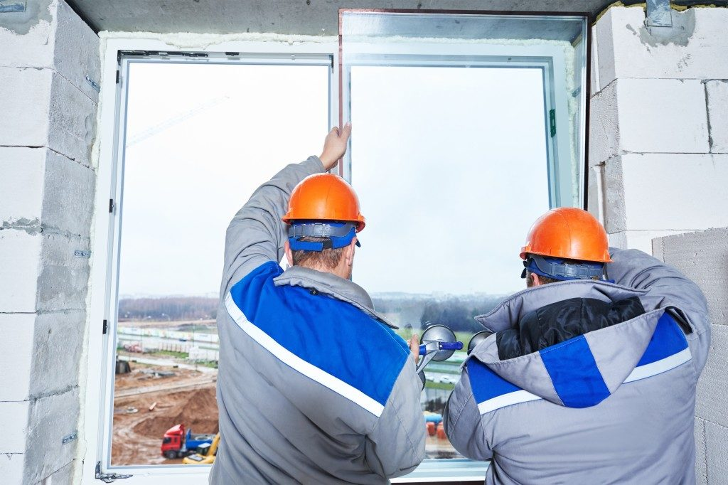 male industrial builders worker at window installation in building construction site
