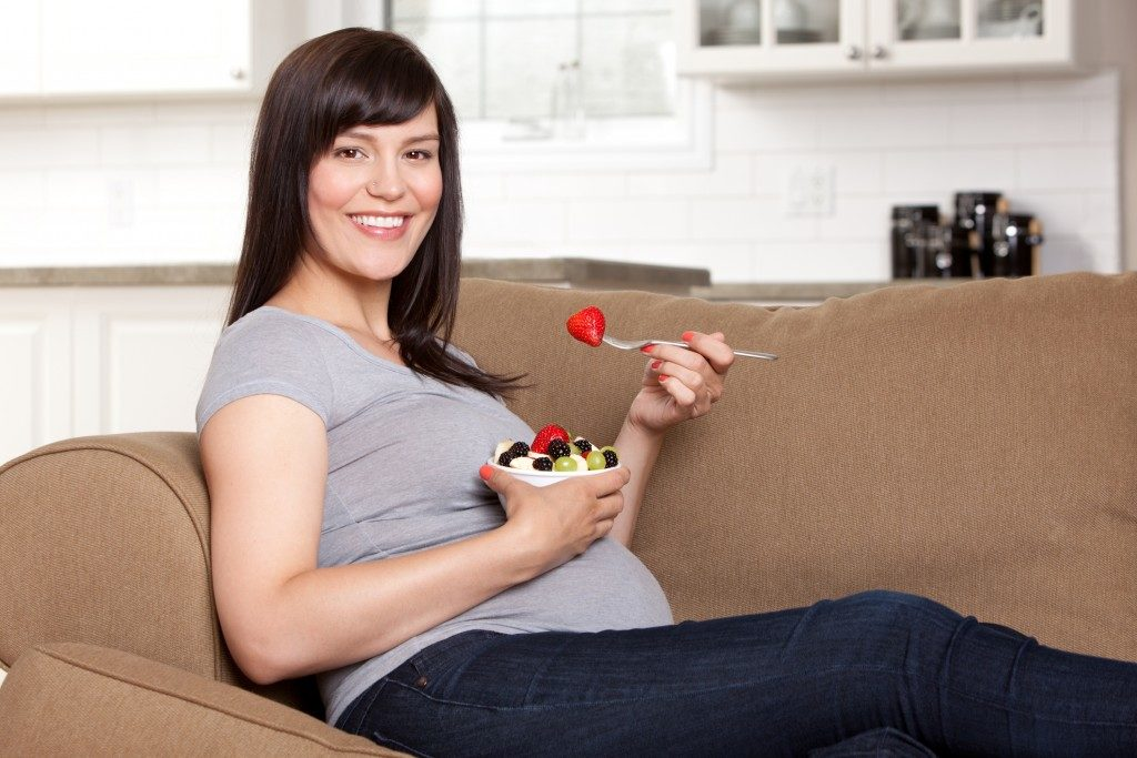 Happy pregnant woman sitting on sofa eating bowl of fresh fruit