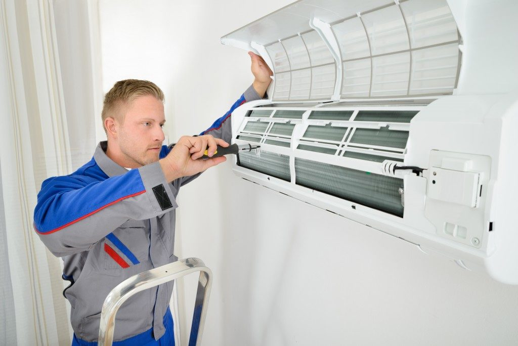 Male electrician repairing air conditioner standing on stepladder