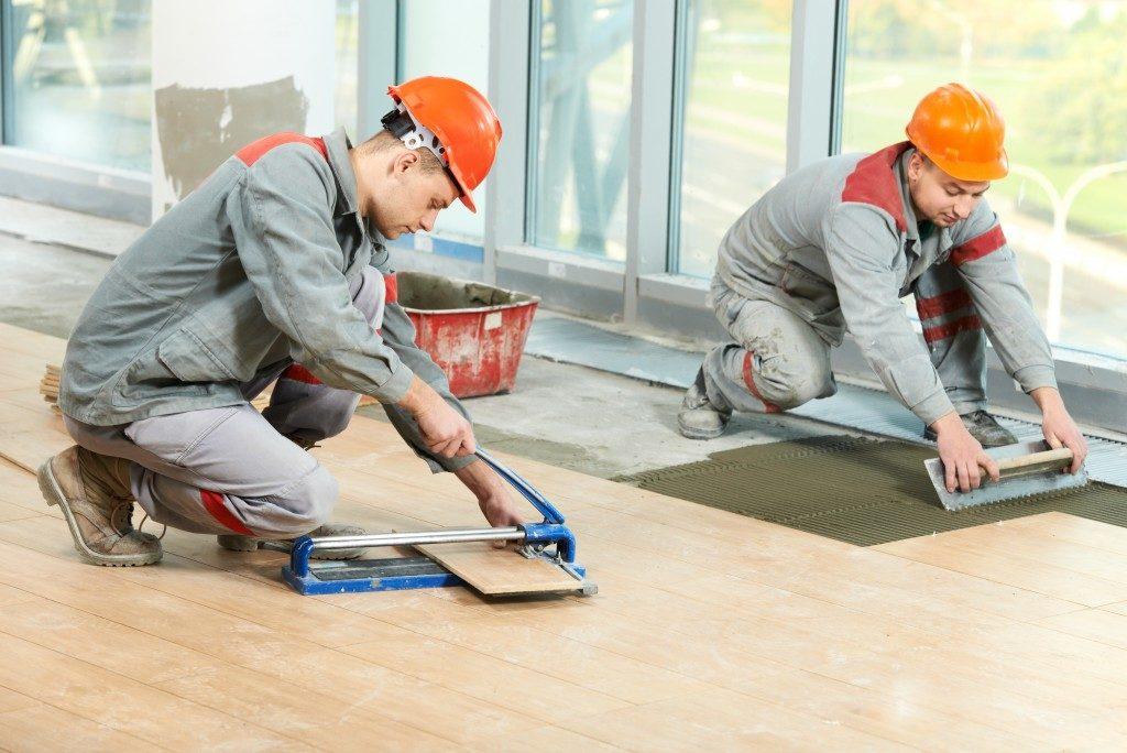 men installing wooden tiles