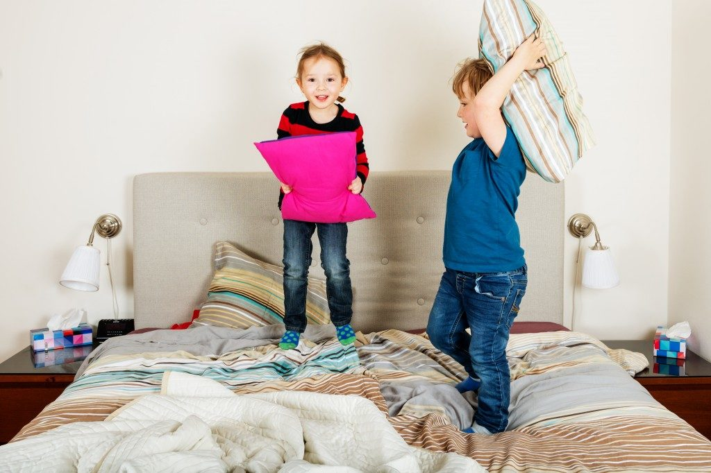 Children having pillow fight on the bed