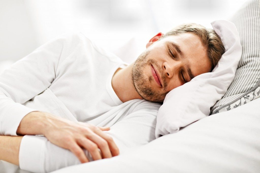 Man sleeping on white bedsheets