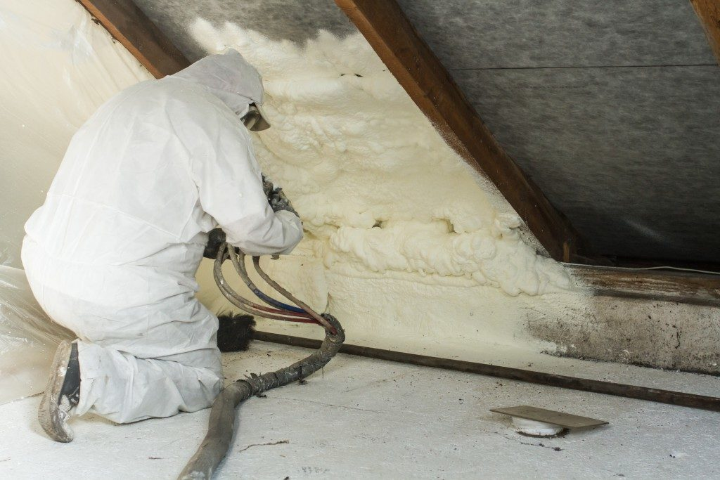 contractor installing insulation in the attic