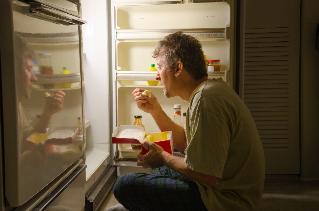 man eating as he sits in front of a refrigerator eating ice cream out of carton
