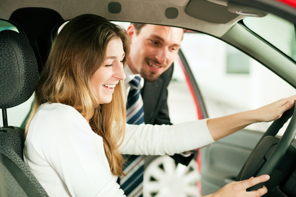 Female client inside car with car agent