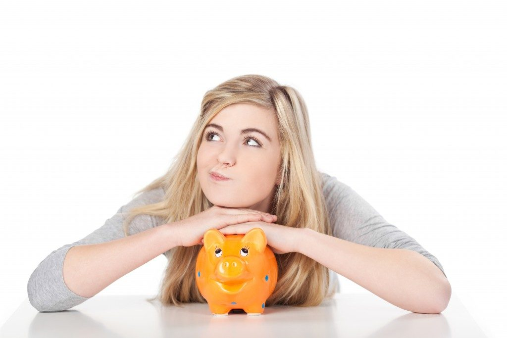Image of a cute teenage girl posing with piggy bank