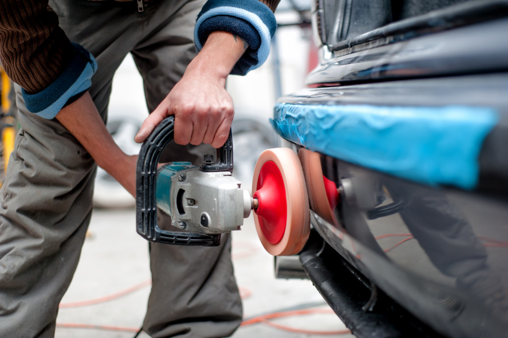 man polishing car exterior