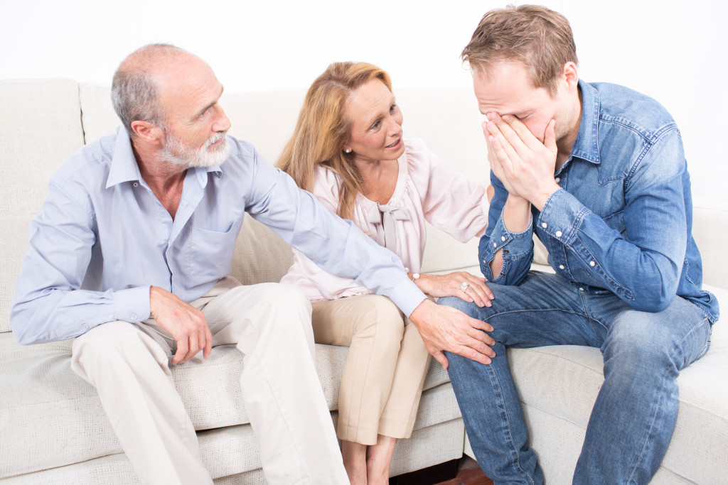 man crying in front of parents